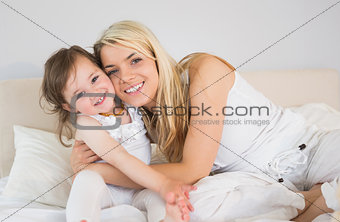 Portrait of happy mother and daughter sitting on bed