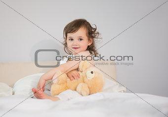 Portrait of cute little girl sitting on bed