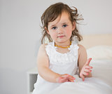 Portrait of cute little girl sitting on bed