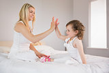 Mother and daughter high fiving on bed