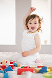 Cute happy girl playing with building blocks on bed