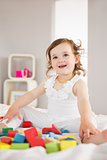 Cute girl playing with building blocks on bed