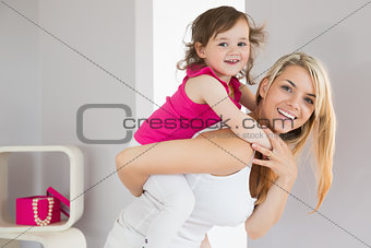 Smiling young woman carrying daughter