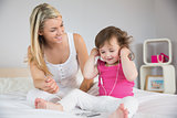 Mother looking at daughter with headphones on bed