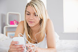 Relaxed woman listening music with mobile phone in bed