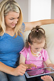 Mother and daughter using digital tablet on couch