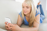 Relaxed woman text messaging in living room