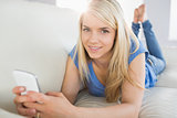 Relaxed beautiful woman text messaging in living room