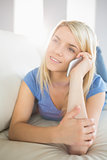 Relaxed woman using mobile phone in living room