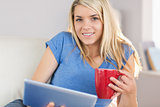 Beautiful woman using digital tablet while drinking coffee at home