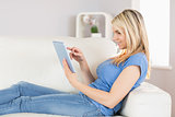 Relaxed woman using digital tablet in living room