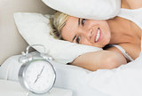 Woman an covering ears with pillow as she looks at alarm clock