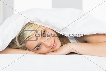 Thoughtful relaxed woman lying in bed
