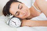 Beautiful woman sleeping in bed with alarm clock
