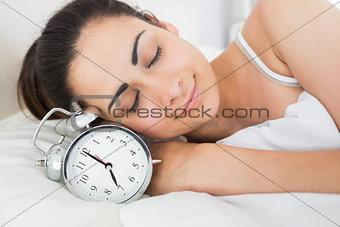 Beautiful woman sleeping in bed with alarm clock