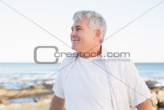 Casual mature man smiling by the sea