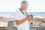 Casual mature man looking at his camera the sea