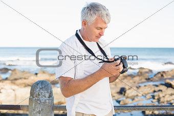 Casual mature man looking at his camera the sea
