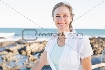 Casual woman smiling at camera by the sea