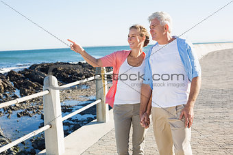 Happy casual couple walking by the coast