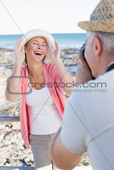 Happy casual man taking a photo of partner by the sea