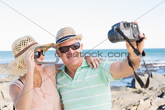 Happy casual couple taking a selfie by the coast