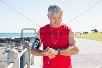 Fit mature man checking the time on the pier