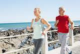 Fit mature couple jogging on the pier