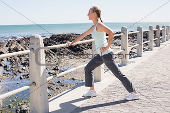 Fit mature woman warming up on the pier