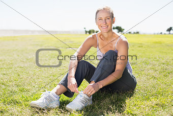 Fit mature woman tying her lace on the grass