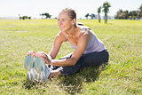 Fit mature woman warming up on the grass
