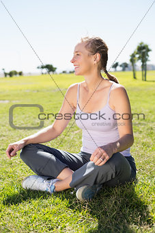 Fit mature woman sitting in lotus pose on the grass