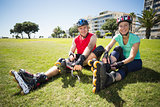 Fit mature couple tying up their roller blades on the grass