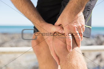 Fit man gripping his injured knee