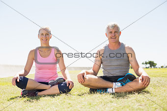 Fit mature couple sitting in lotus pose on the grass