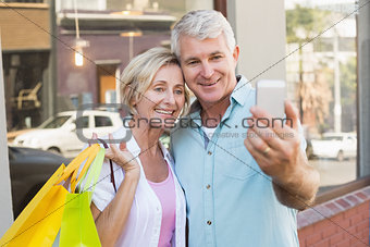 Happy mature couple taking a selfie together in the city