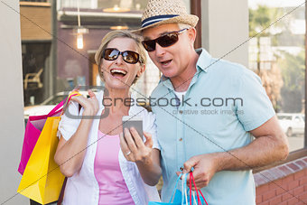 Happy mature couple looking at smartphone together in the city