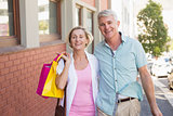 Happy mature couple walking with their shopping purchases