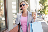 Happy mature woman walking with her shopping purchases