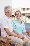 Happy mature couple sitting on bench in the city
