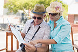 Happy tourist couple looking at map in the city