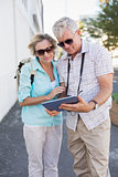 Happy tourist couple using tablet in the city