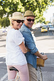 Happy mature couple going for a bike ride in the city