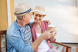 Happy mature couple drinking coffee on a bench in the city
