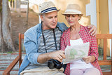 Happy tourist couple looking at map on a bench in the city