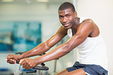 Portrait of man working out on exercise bike at gym
