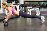 Side view of woman doing push ups with kettle bells in gym