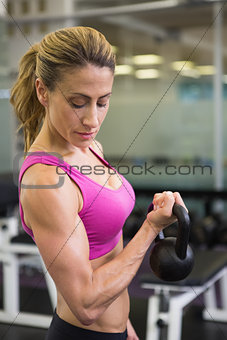 Fit woman lifting kettle bell in gym