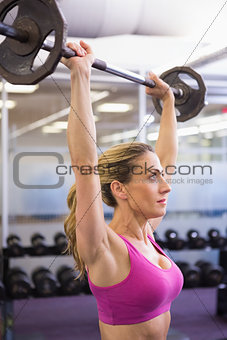 Fit young woman lifting barbell in gym