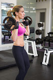 Fit young woman lifting barbell in the gym